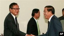 PM Kamboja Hun Sen (kanan) berjabat tangan dengan pemimpin oposisi Sam Rainsy sebelum pembicaraan hari kedua terkait upaya penyelesaian krisis politik negara itu di Phnom Penh (17/9).