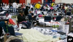 People rest at the George R. Brown Convention Center that has been set up as a shelter for evacuees escaping the floodwaters from Tropical Storm Harvey in Houston on Tuesday, Aug. 29, 2017.
