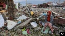 Một người dân làng ngồi bên cạnh đống đổ nát sau khi ngôi nhà của bà bị phá huỷ sau trận động đất tại Indonesia.
