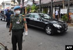 Para petugas keamanan berjaga di dekat mobil kepresidenan yang membawa Presiden Joko Widodo usai membagikan bantuan kepada warga yang terdampak Covid-19, di Jakarta, 18 Mei 2020. (Foto: Adek Berry/AFP)