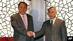 ທູດພິເສດເກົາຫລີໃຕ້ ທ່ານWi Sung-lac (ເບື້ອງຂວາ) ຈັບມື ກັບທ່ານ Ri Yong Ho ທູດພິເສດເກົາຫລີ ເໜືອທີ່ສະໂມສອນ ເອກກະຊົນ Chang An ທີ່ກຸງປັກກິງ, ຈີນ. ວັນທີ 21 ກັນຍາ 2011.