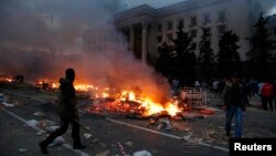 Demonstrant ispred zapaljenog šatora pro-ruskih separatista, u blizini zgrade sindikata u Odesi