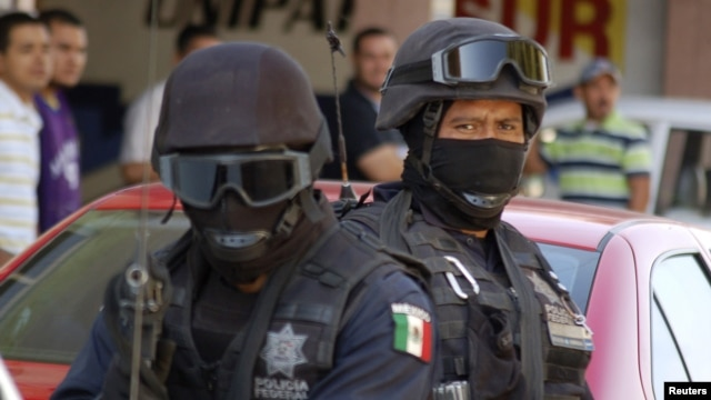 FILE - Mexican federal police officers are seen standing guard during a raid.