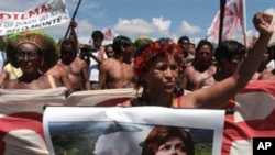 A member of the Kaiapo tribe holds a poster showing a picture of Brazilian President Dilma Rousseff during a protest against the construction of Belo Monte hydroelectric dam in Brasilia, Brazil, Tuesday Feb. 8, 2011.