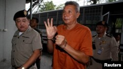 Thanat Thanawatcharanon, also known by his stage name Tom Dundee, a Thai actor, singer and political activist, who was accused of insulting the king in public speech, gestures as he arrives at the criminal court in Bangkok, Thailand, June 1, 2016.