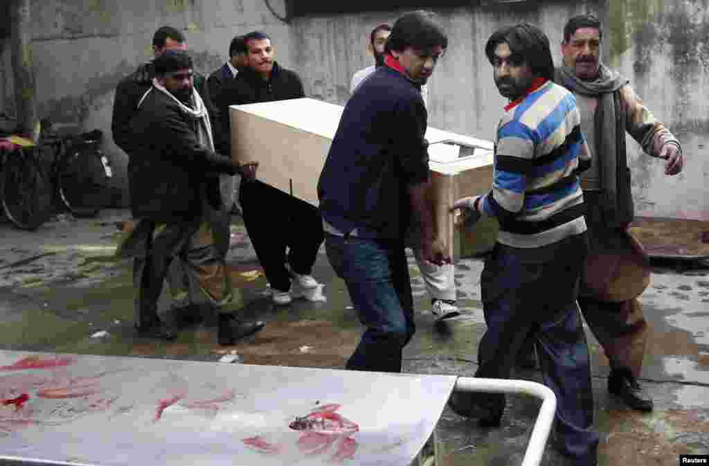 Relatives carry the casket of a victim who was killed in a bomb attack, at a hospital morgue in Rawalpindi, Pakistan, Jan. 20, 2014.