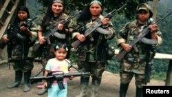 En esta foto confircada por la policía colombiana, guerrilleras de las FARC posan con sus armas junto a una niña. Las menores son obligadas a brindar favores sexuales a sus 'superiores', señalan declaraciones.