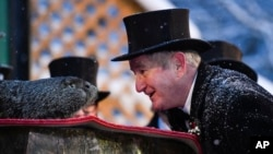 Groundhog Club President Jeff Lundy interacts with Punxsutawney Phil, the weather prognosticating groundhog, during the 135th celebration of Groundhog Day in Punxsutawney, Pa. Tuesday, Feb. 2, 2021. (AP Photo/Barry Reeger)