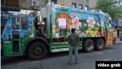 Misha Tytyunik (MDot), seniman Ukraina di New York, berdiri di depan truk sampah yang menjadi kanvas bagi lukisannya. (Foto: videograb)