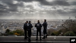 FILE - French police officers stand guard near the church of Sacre Coeur, on top of Montmartre hill, in Paris, Nov. 18, 2015, days after coordinated terrorist attacks killed 130 people in the French capital.