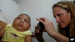 Pediatrician Alexia Harrist from the United States' Centers for Disease Control and Prevention (CDC) takes a picture of 3-month-old Shayde Henrique who was born with microcephaly, after examining him in Joao Pessoa, Brazil, Feb. 23, 2016.