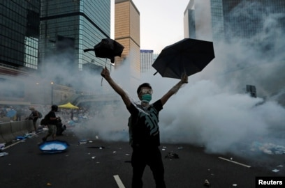 一名抗议者在香港警察向和平示威的民众施放催泪弹后举起了雨伞。(2014年9月28日)