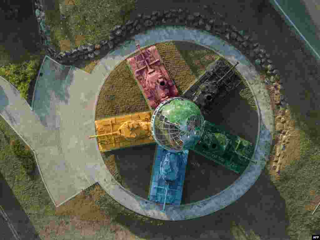 An aerial view of an art installation featuring Korean war-era tanks painted in different colors around a globe with a slogan reading: 'Peace All Around the World', at the Peace dam, north of Hwacheon near the Demilitarized Zone (DMZ) separating North and South Korea, May 21, 2017.