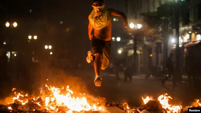 A demonstrator jumps over trash set afire during protests against poor public services, police violence and government corruption, in Sao Paulo, Brazil, June 18, 2013.