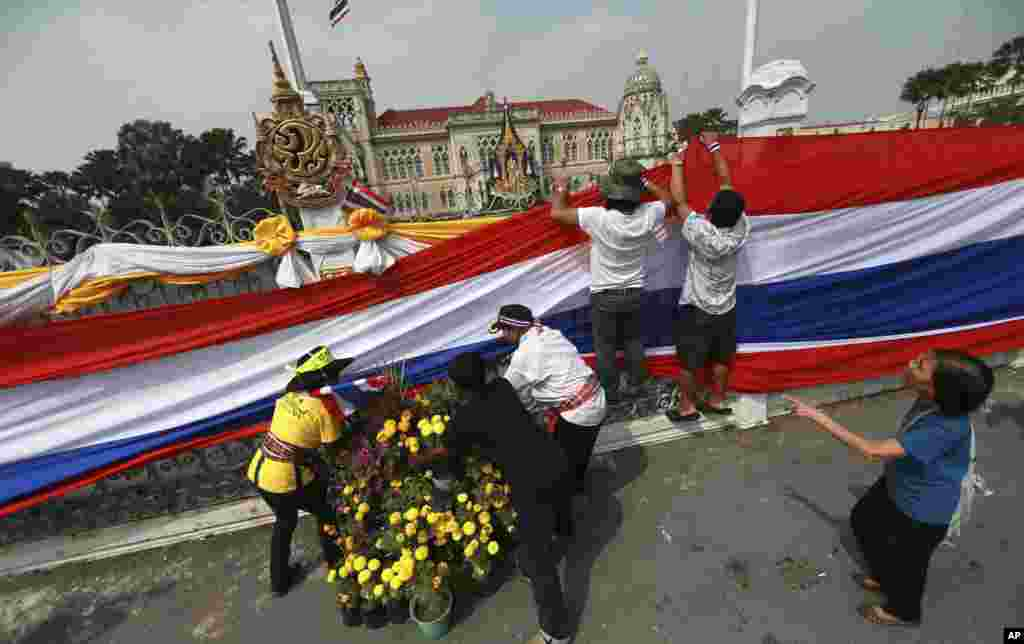 Anti-government protesters hold a long Thai national flag on the gate and fence around the prime minister's office, known as Government House, in Bangkok, Dec. 13, 2013.