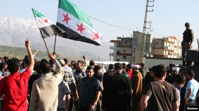 Residents block the road and wave Syrian opposition flags to protest what they call Lebanese shipments of diesel to the Syrian government a the Masnaa Border Crossing on April 28, 2013.