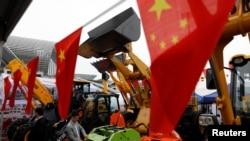 Bendera China terlihat di depan kendaraan konstruksi selama China Import and Export Fair, juga dikenal sebagai Canton Fair, di selatan kota Guangzhou, China 16 April 2018. (Foto: REUTERS/Tyrone Siu)