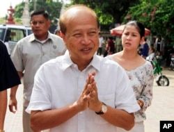 FILE - In this Sunday, June 3, 2012, Cambodian Prince Norodom Ranariddh greets people before casting his ballot in local elections at the Wat Than temple in Phnom Penh, Cambodia. (AP Photo)