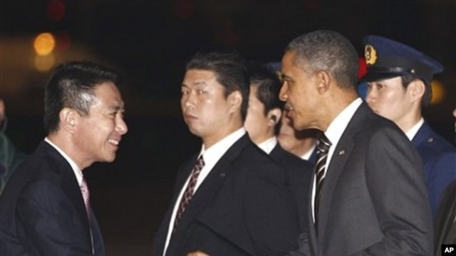 U.S. President Barack Obama is greeted by Japanese Foreign Minister Seiji Maehara as he arrives at Haneda Airport in Tokyo, 12 Nov 2010