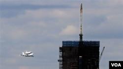 Enterprise yang digendong Boeing 747 terbang dekat One World Trade Center yang sedang dibangun di Ground Zero, NYC , Jumat (27/4).