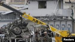 Petugas keamanan Afghanistan berdiri di dekat kendaraan yang hancur akibat ledakan bom di Kabul, Afghanistan (19/4).