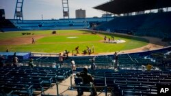 People work near a statue of Cuban baseball fan and entertainer Armando Luis Torres Torres at the Latinoamericano stadium, March 16, 2016. A friendly game will be played on March 22 between the Cuban national baseball team and the Tampa Bay Rays, in Havan