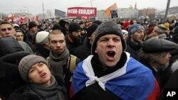 ហ្វុងបាតុករស្រែកពាក្យស្លោកនៅ Bolotnaya square នៃក្រុងមូស្កូ ថ្ងៃទី១០ ធ្នូ ២០១១។ ផ្ទាំងបដានៅខាងក្រោយអានថា «ចុះចេញពីអំណាច ពូទីន!»។