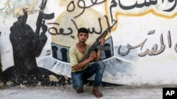 A Free Syrian Army fighter poses for a photograph in front of a painting left by the IS militants in Jarablus, Syria, Wednesday, Aug. 31, 2016.