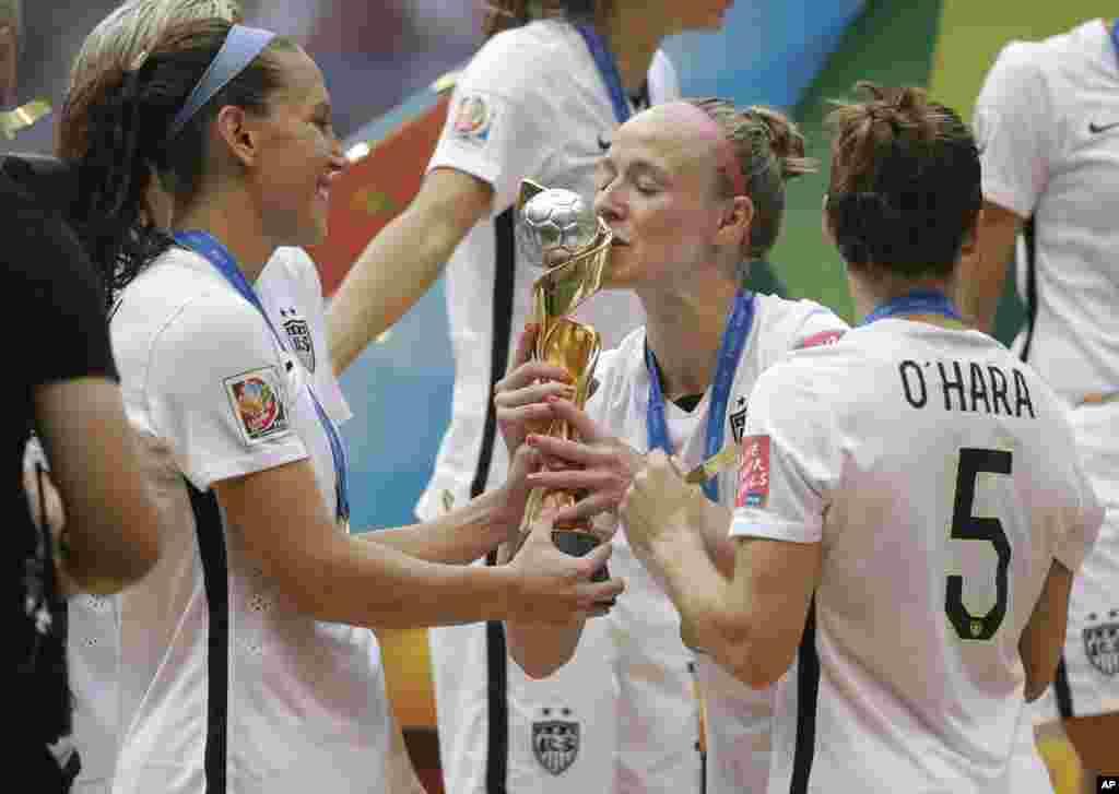Jogadora americana Becky Sauerbrunn beija o troféu enquanto as jogadoras Kelley O'Hara e Lauren Holiday esperam a sua vez, depois da vitória por 5-2 dos EUA contra o Japão no Mundial Feminino da FIFA em Vancouver, Canadá, no Domingo, 5 de Julho, 2015.