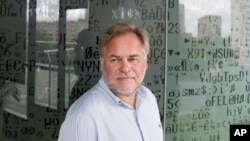 FILE - Eugene Kaspersky, Russian antivirus programs developer and chief executive of Russia's Kaspersky Lab, stands in front of a window decorated with programming code's symbols at his company's headquarters in Moscow, July 1, 2017.