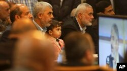 Yehiya Sinwar, left, a top Hamas official in Gaza, holds his son's Ibrahim, while sitting near Ismail Haniyeh, right, a former top Hamas official in Gaza, while listening to Khaled Mashaal, the outgoing Hamas leader in exile, during his news conference in Doha, Qatar, while display on a screen in Gaza City, May 1, 2017. Hamas unveiled what had been billed as a new, seemingly more pragmatic political program.
