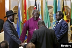 FILE - South Sudan's rebel leader Riek Machar, right, and South Sudan's President Salva Kiir, left, hold a priest's hands as they pray before signing a peace agreement in Addis Ababa, May 9, 2014.