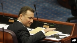 Macedonian Prime Minister Nikola Gruevski gestures, while attending a session in the parliament after resignation of two ministers from Prime Minister's cabinet and a senior state security official, on Wednesday, May, May 13, 2015, in Skopje, Macedonia.