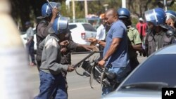 A cameraman is hit by the police during demonstrations in Harare on Aug. 3, 2016.