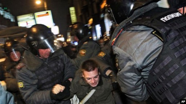 Police officers detain a protester during a rally at Triumphal Square in downtown Moscow, Wednesday, Dec. 7, 2011.