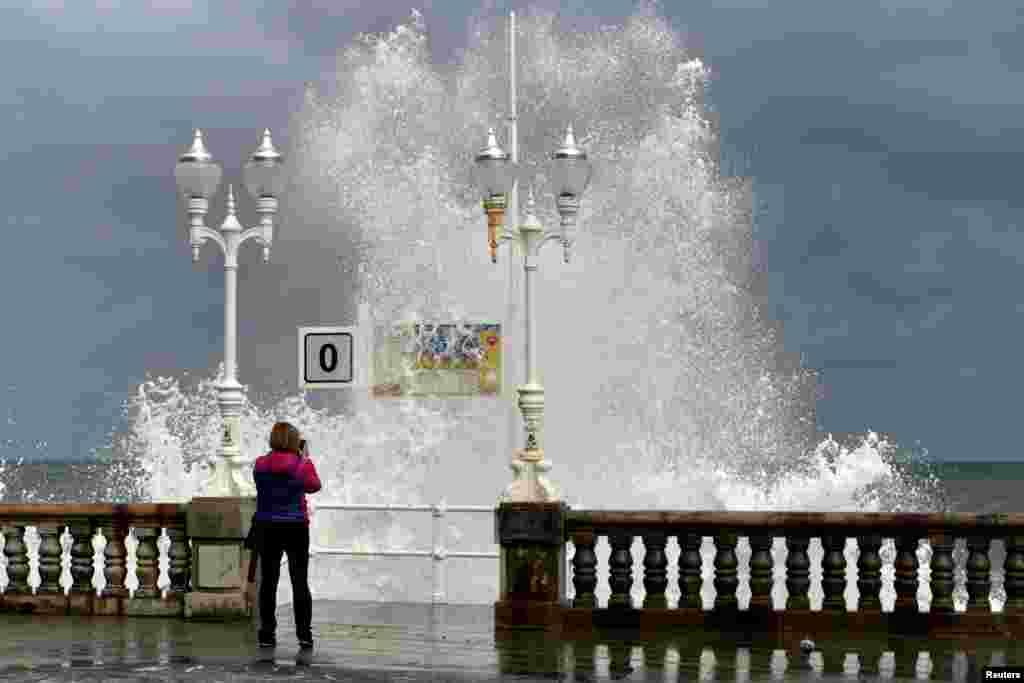 Seorang perempuan mengambil foto saat ombak besar menghantam pantai San Lorenzo di Gijon, Spanyol.