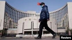 一名戴著口罩的男子走過北京的中國人民銀行總部。(2020年2月3日)