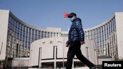 一名戴着口罩的男子走过北京的中国人民银行总部。(2020年2月3日)