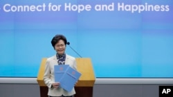 Hong Kong Chief Executive Carrie Lam poses with copies of her policy address at a news conference in Hong Kong, Oct. 11, 2017.