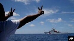 菲律宾船上人员向阻止他们进入南中国海第二托马斯浅滩(仁爱礁)的中国海警船打手势。(2014年3月29日)