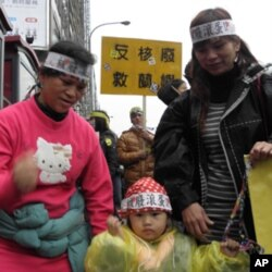 蓝屿原住民黄美娇(左)带着孩子参加游行