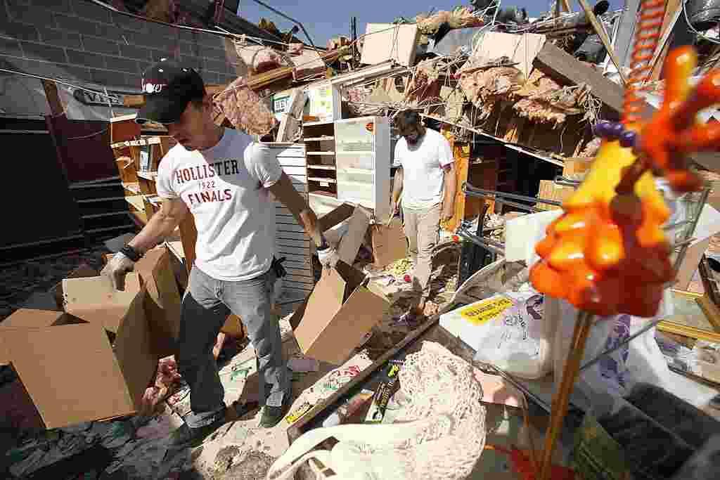 Tres socios recogen los escombros de su tienda en Branson, Missouri.