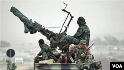 Pemberontak Libya menaiki truk yang memuat artileri anti-pesawat terbang dalam perjalanan mereka ke Ras Lanuf, di Libya timur.