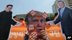 A protester wearing a mask of U.S. President Donald Trump performs with cut-out photos of North Korean leader Kim Jong Un and South Korean President Moon Jae-in, right, during a rally in Seoul, South Korea, May 25, 2018.
