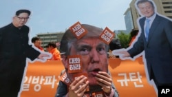 "A protester wearing a mask of U.S. President Donald Trump, center, performs with cut-out photos of North Korean leader Kim Jong Un and South Korean President Moon Jae-in, right, during a rally against the United States' policies against North Korea near the U.S. embassy in Seoul, South Korea, May 25, 2018. The signs read ""Apology."""