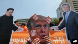 Nan Sewoul, Kore di Sid, yon manifestan ak yon mask ki reprezante Preszidan Donald Trump (nan mitan) ki tap bay yon show nan lari ak foto lidè Kore di Nò a Kim Jong Un (agoch) ak Prezidan Kore di Sid la, Moon Jae-in (adwat), pandan yon pwotestasyon kont politik Lèzetazini kont Kore di Nò.
