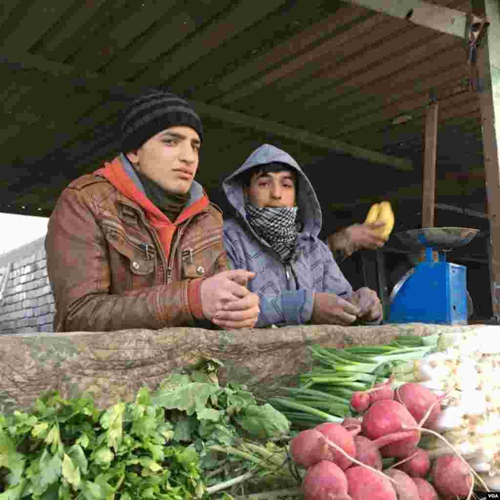 Young adults talk at the local market in Qayyarah town, south of Mosul, December 2016. (Kawa Omar/VOA)