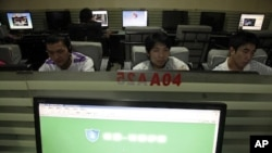 In this photo taken, July 14, 2010, Chinese men use computers at an internet cafe in Beijing, China. China's Twitter-like microblogs are facing new restrictions by the government.