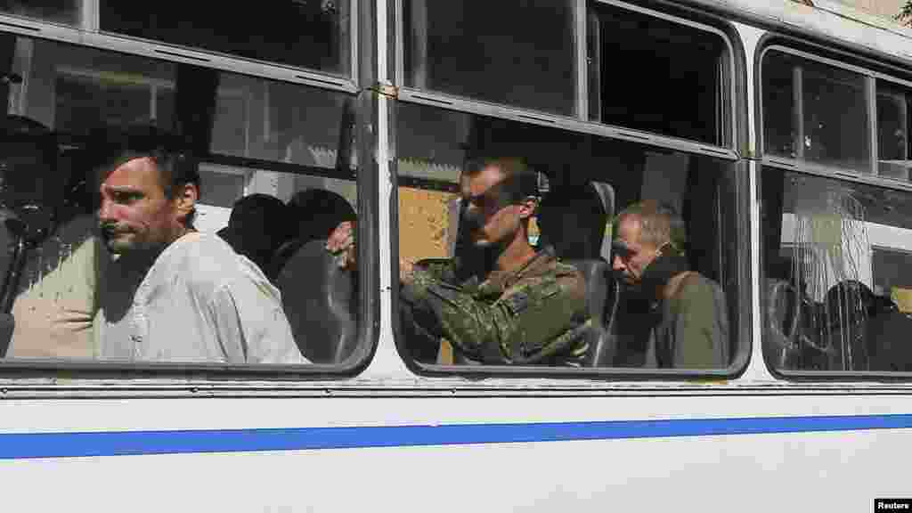 Ukrainian prisoners of war sit in a bus after being escorted for a forced-march across central Donetsk, Ukraine, Aug. 24, 2014.