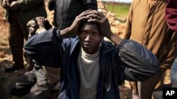 A suspected mercenary from Chad keeps his hands on his head after being detained by Libyan militia member from the forces against Libyan leader Moammar Gadhafi at a roadblock near Marj in eastern Libya, February 27, 2011
